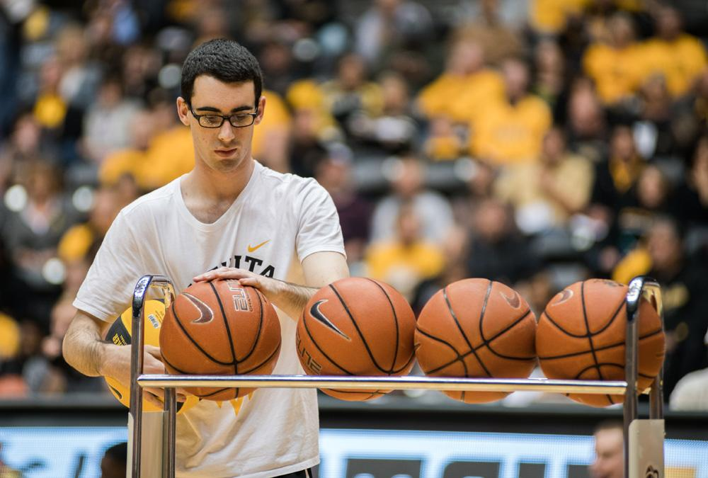 Manager Matt Poland prepares basketballs during Shocker Madness.