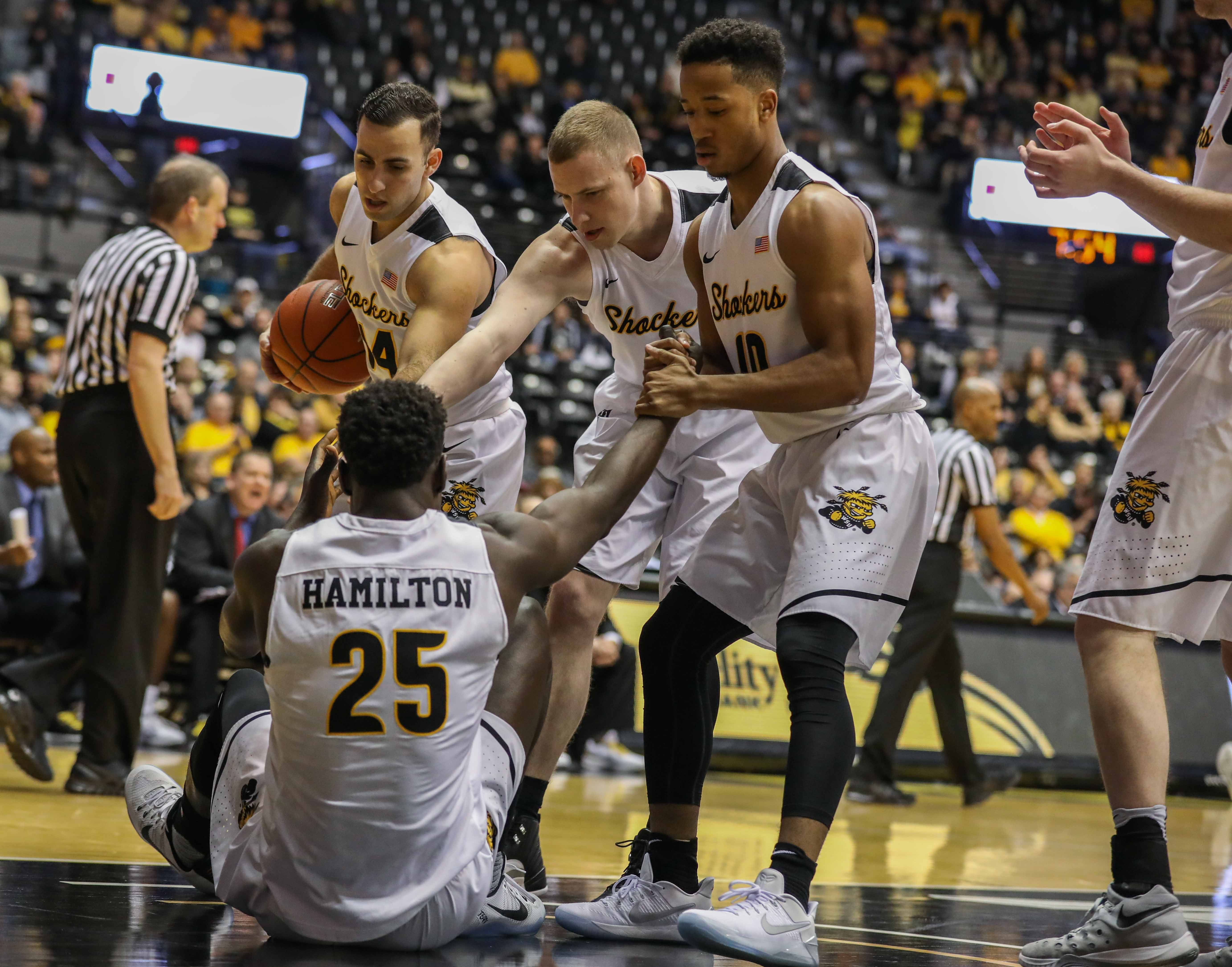 Teammates help Wichita State's Eric Hamilton (25) to his feet after he tangled with an Illinois State player.