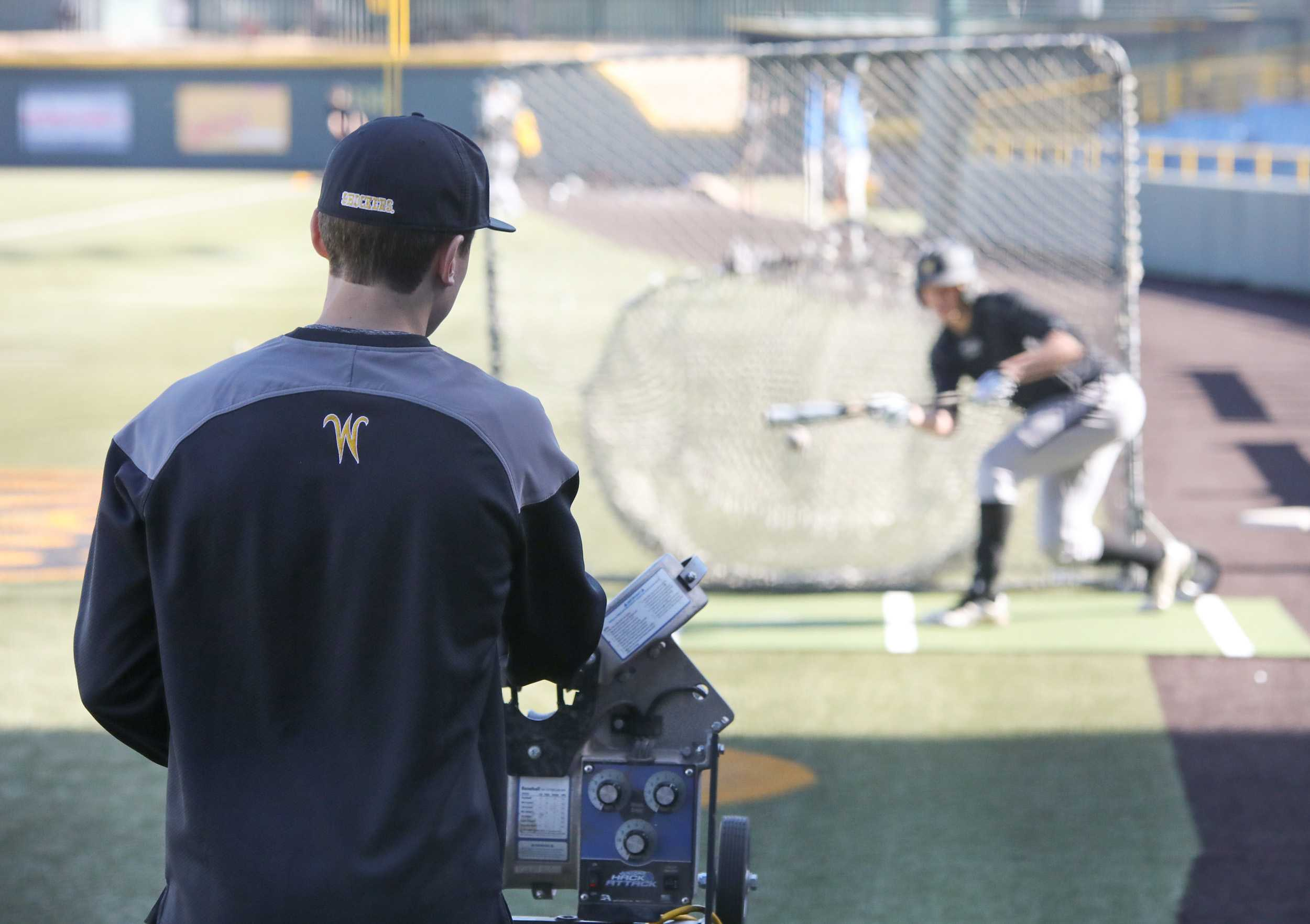 Wichita State baseball manager Nathan Brisco loads the pitching machine while a player takes bunting practice on Feb. 10, 2017. Brisco is a transfer student from Kansas City Community College where he redshirted on their baseball team as a freshman last year. Though a shoulder injury prevented Brisco from playing at KCCC, he has still found a way to be involved with baseball here at WSU.