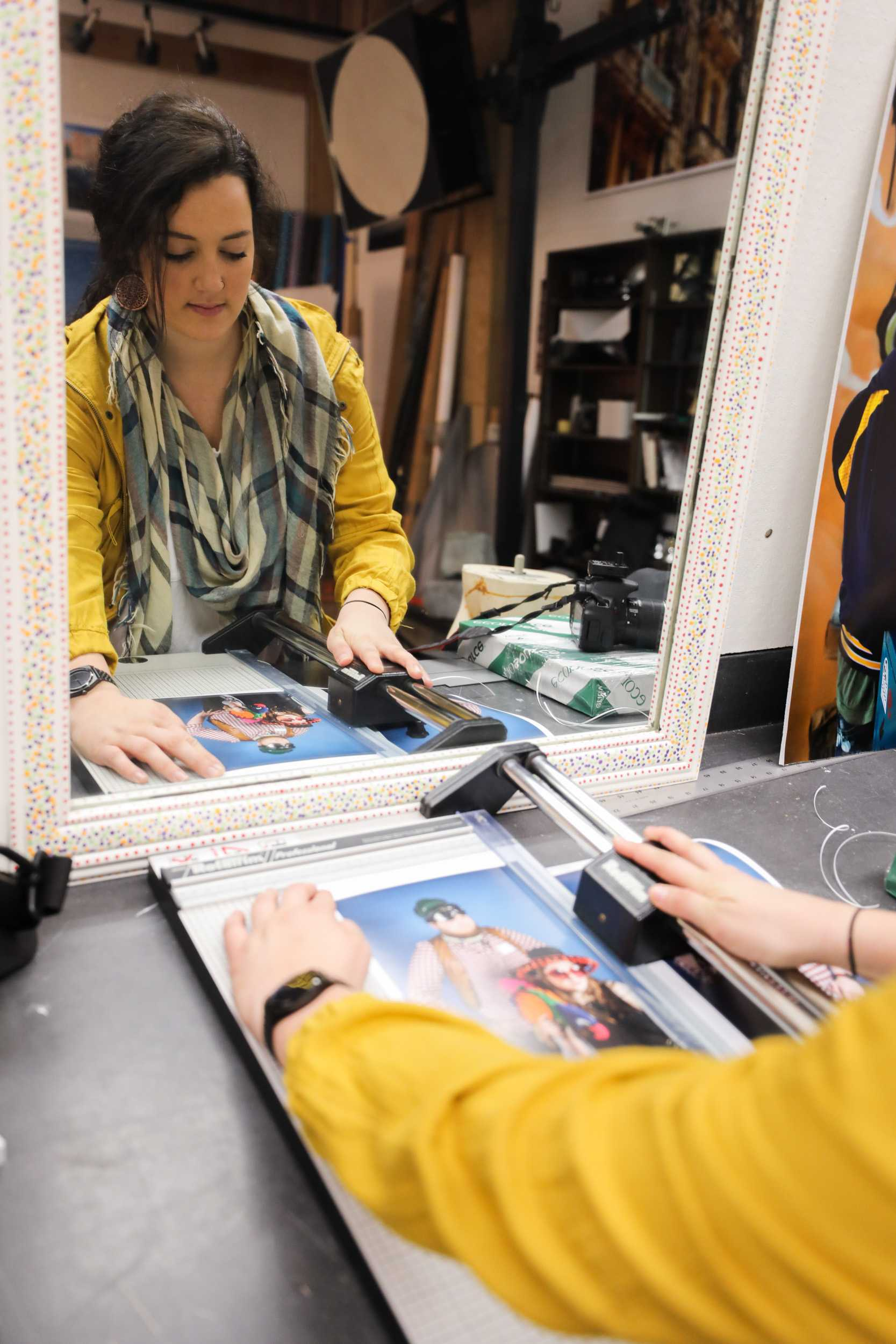 Mariah Drussel, Wichita State senior, cuts a print of a photo during the funky photo shoot in McKnight Art Center. The photo shoot was part of the ADCI open house held on Saturday. (Feb. 18, 2017)