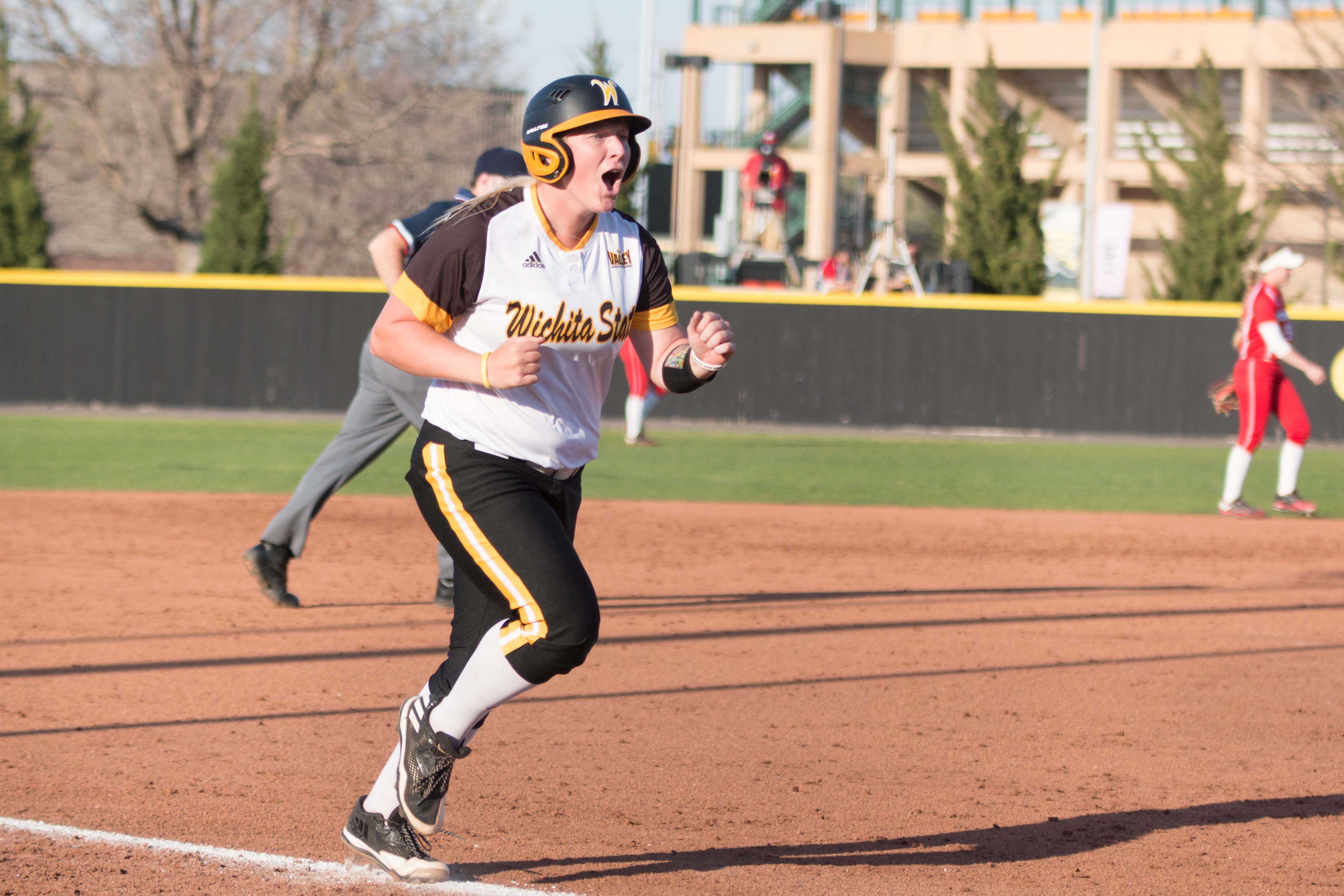 Senior Macklin Hitz cheers as she  runs to home base after hitting a homerun against Nebraska.