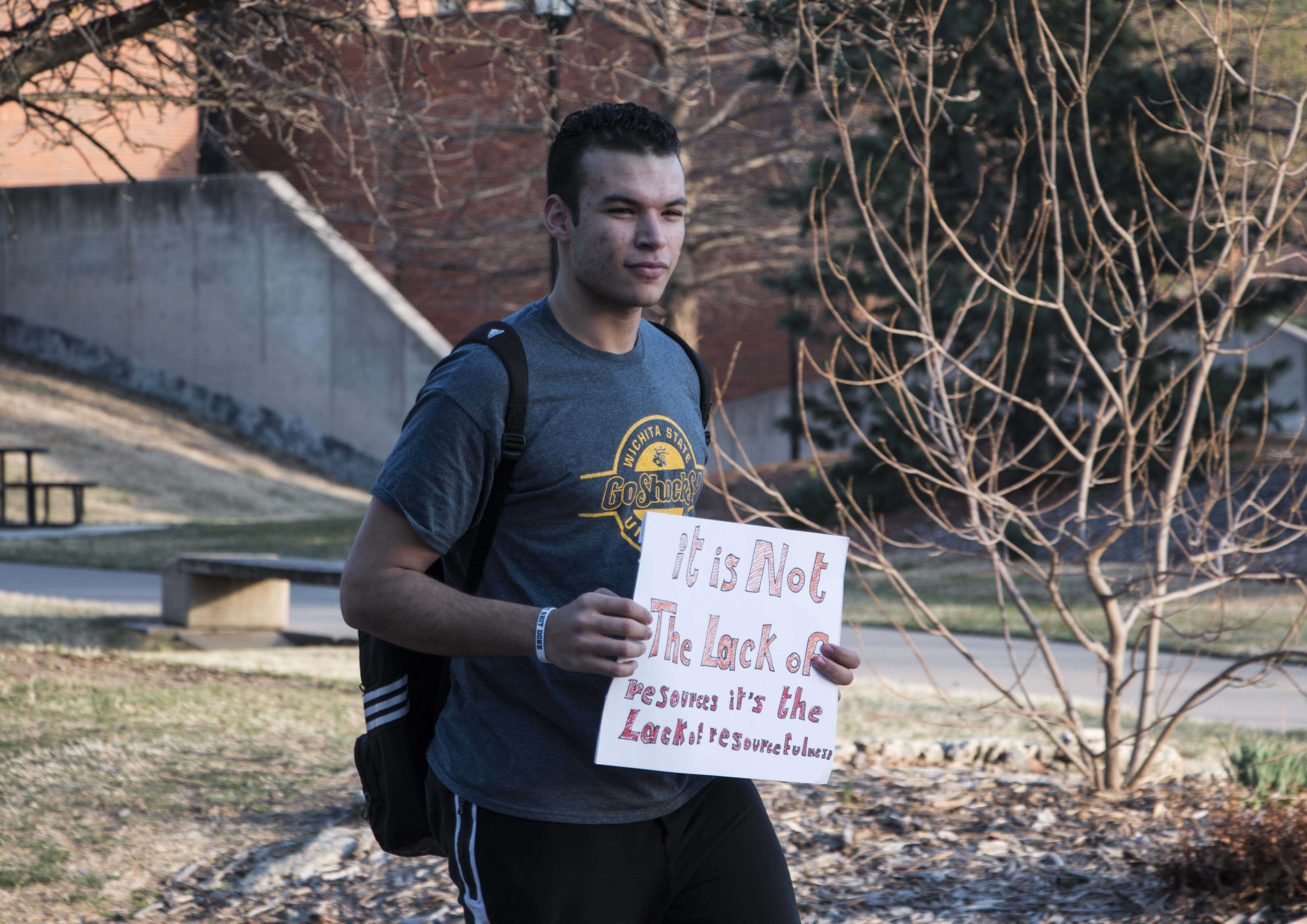 Amr Wahba, a protester, holds a sign in opposition to the construction of a YMCA facility on Wichita State's campus. The proposal calls for a student fee of $7.75 per credit hour to be added to financially support the facility.