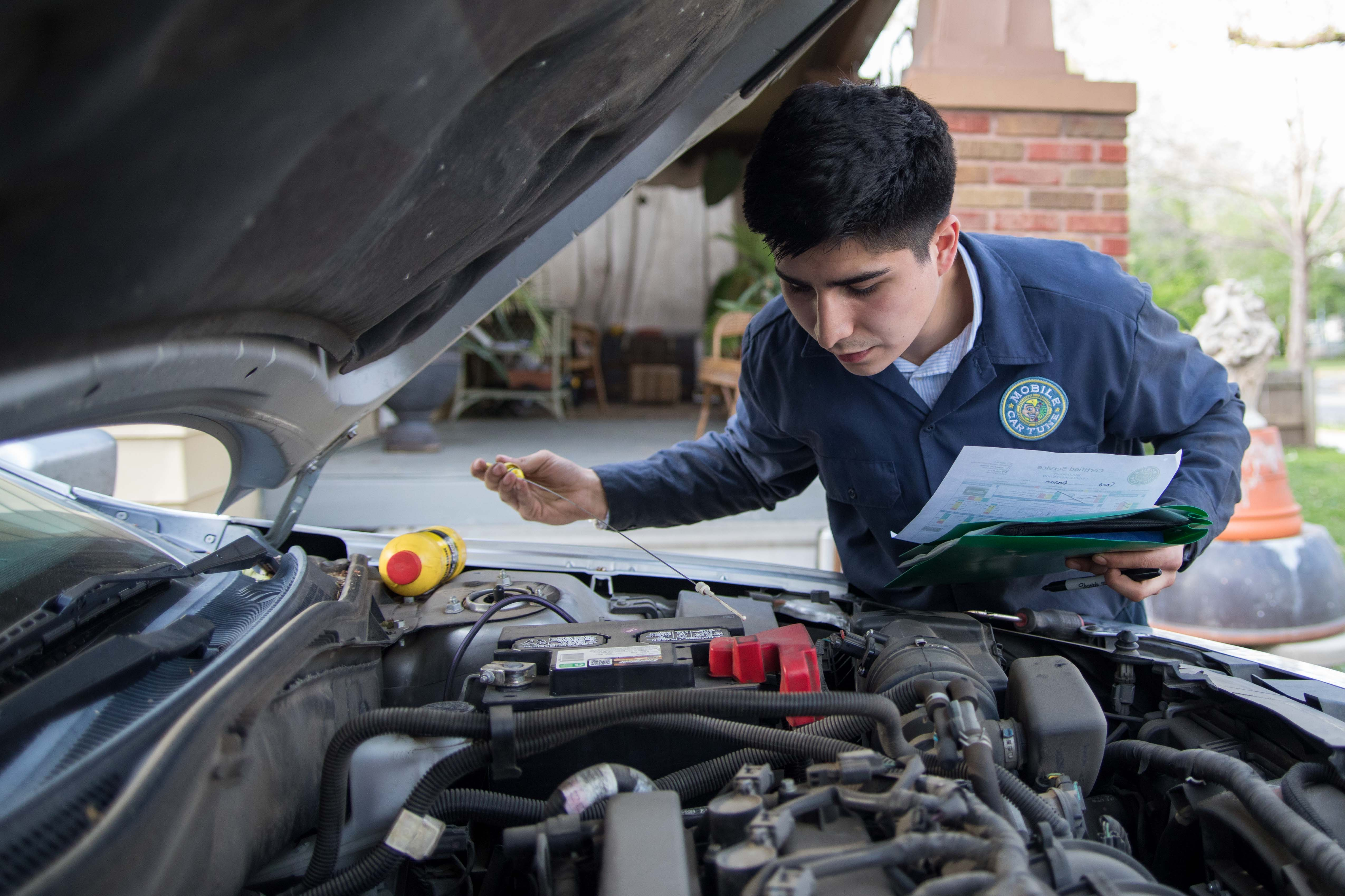 Ernie Cisneros checks the transmission fluid for his client Dan Edwards on Wednesday evening. Cisneros owns a business called Mobile Car Tune that performs car maintenance services at people's homes.