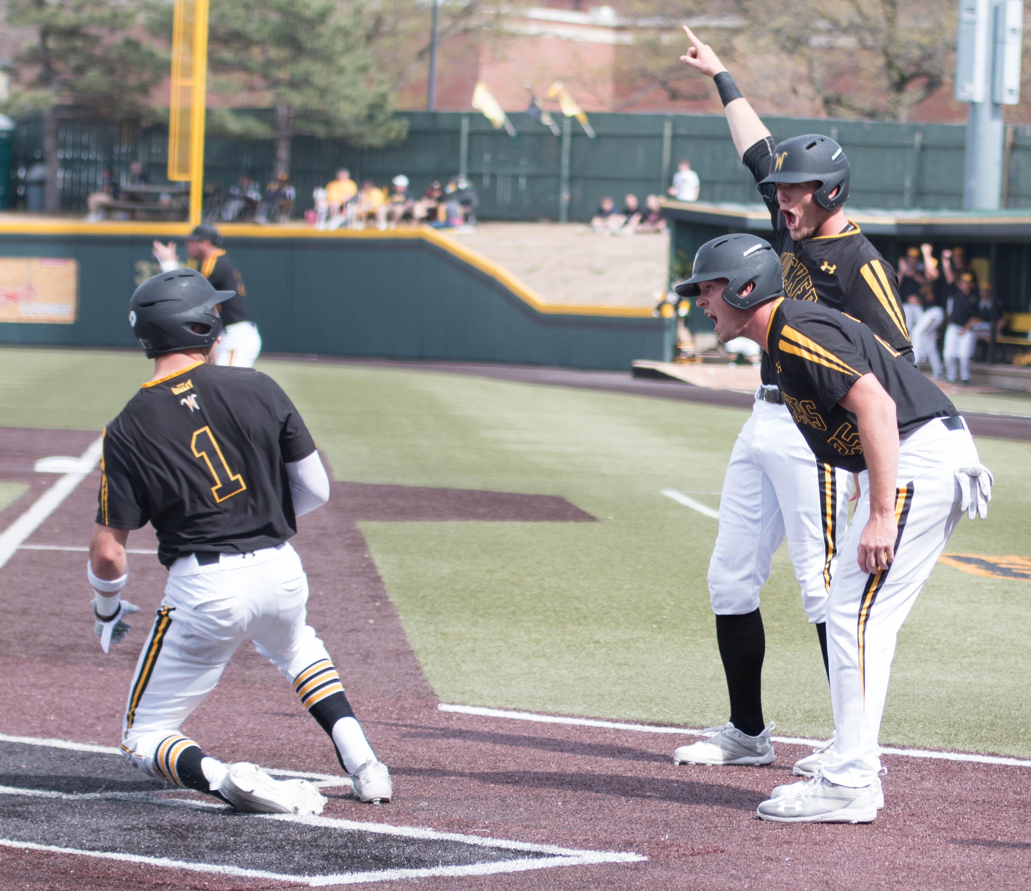 Greyson Jenista and Dayton Dugas meet Travis Young at home plate after scoring against Southern Illinois. (File photo)