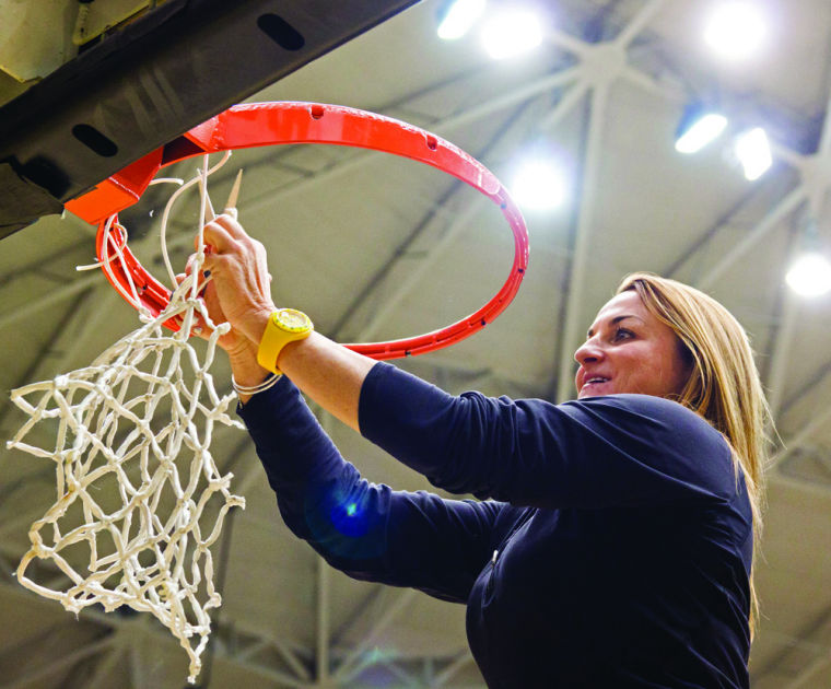 Wichita State womens basketball coach Jody Adams cuts down nets in Koch Arena during a pep rally on Wednesday. The rally was to celebrate the Shockers first conference title in school history.
