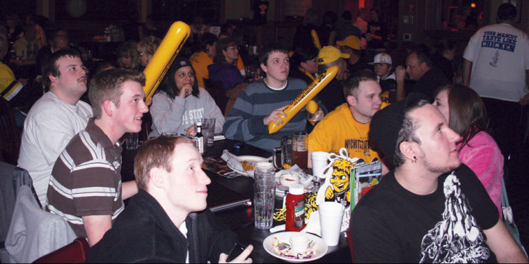 Shocker fans atentively watch the men's basketball game at the WSU Alumni Association watch game party located at Fox and Hound.