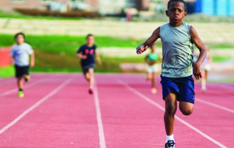 A child sprints toward the finish line during the Shocker Track Club Tuesday evening at Cessna Stadium. The Track club is hosted by Wichita State track students.