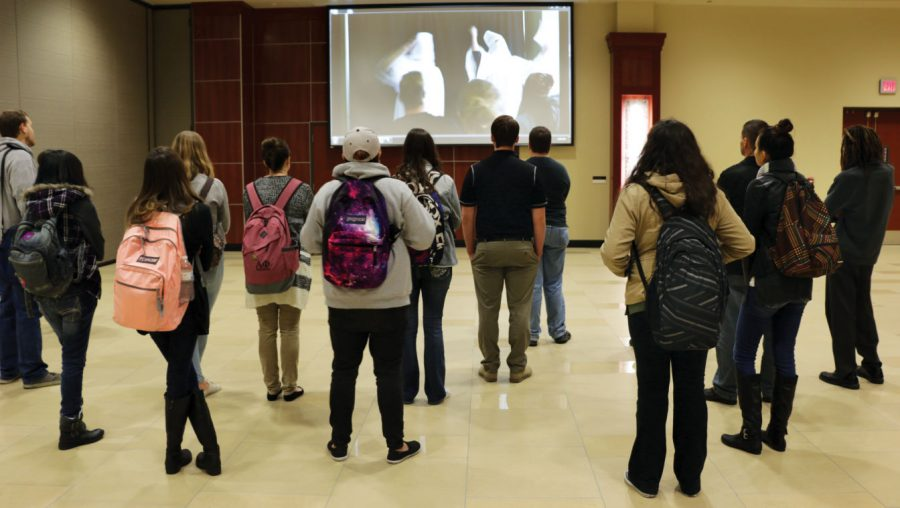 Attendees watch an informative video about the Ku Klux Klan on Tuesday at the Tunnel of Oppression in the Rhatigan Student Center.