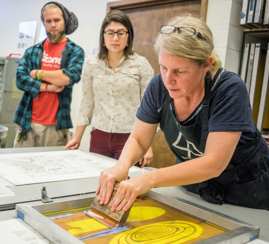 Printmaker artist Ashley Nason adds water-based paint during her demonstration on how to make lithography prints during her ShockPress workshop Tuesday. Nason's work explores the evolution of our environment as a result of overconsumption, pollution and the misuse of natural resources.
