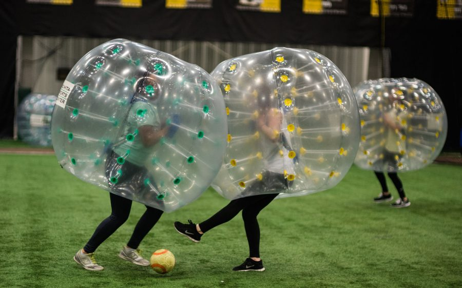 """A member of the green team, left, smashes into her opponent during a match of bubble soccer Wednesday at the Bombardier Learjet Indoor Practice Facility. Competitors compete in a soccer match while surrounded by a large, inflatable """"bubble."""""""