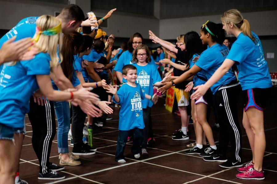 Participants give high-fives to children impacted by the Children's Miracle Network on Saturday afternoon at Charles Koch Arena. Shockerthon is a 12-hour event in which participants stand the entire time and collect money for the program which aids children with disabilities.