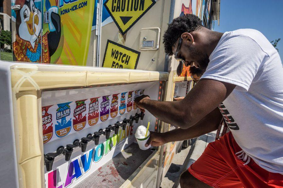 Ayron Lewallen, political science major, adds flavoring to a shaved ice dessert from Kona Ice during the opening of the WSU Food Truck Plaza.