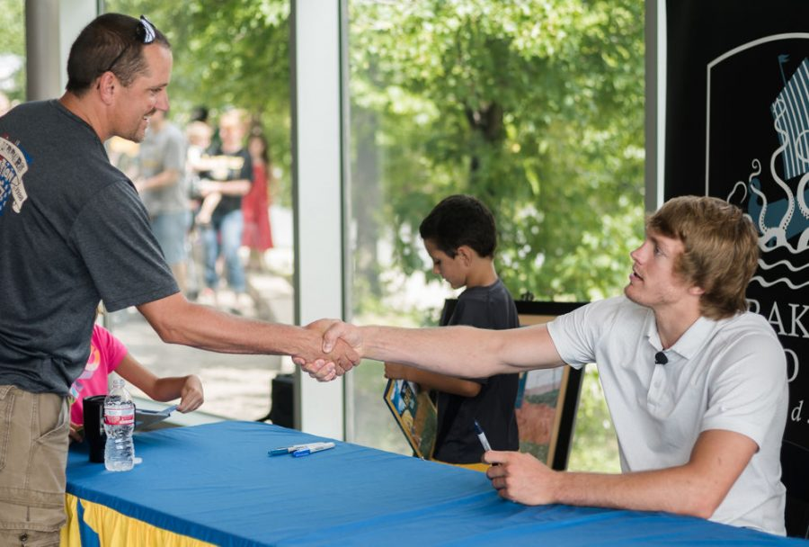 Former Shocker basketball player Ron Baker shakes the hand of a fan during the children's book signing event at the Exploration Place Friday morning. The book is called