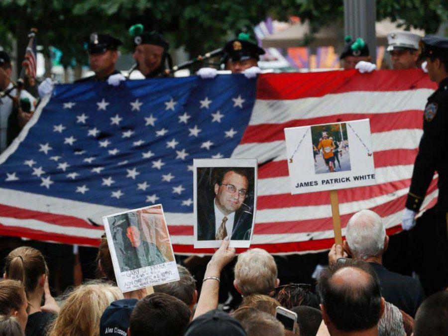 Mourners hold photos of their loved ones during the 15th anniversary of the attacks of the World Trade Center at the National September 11 Memorial, Sept. 11, 2016, in New York.