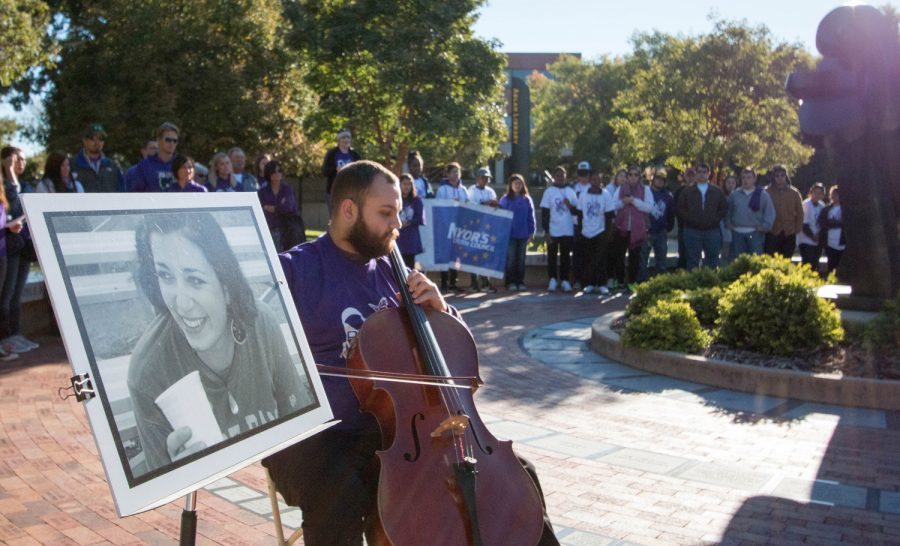 Josh+Mitchell%2C+WSU+student%2C+plays+cello+next+to+a+picture+of+Jana+Mackey%2C+the+victim+of+domestic+violence.+Mitchell+played+along+the+Purple+Mile+on+Saturday+morning%2C+at+WSU.