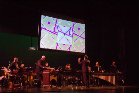 """Gerald Scholl directs the Impulse Percussion Group Sunday evening as they perform """"Palace of Nine Perfections"""" by Eric Ewazen. Laura Scholl's Performative Drawings play on a screen in the background. The drawings are reactionary to what the musicians play."""