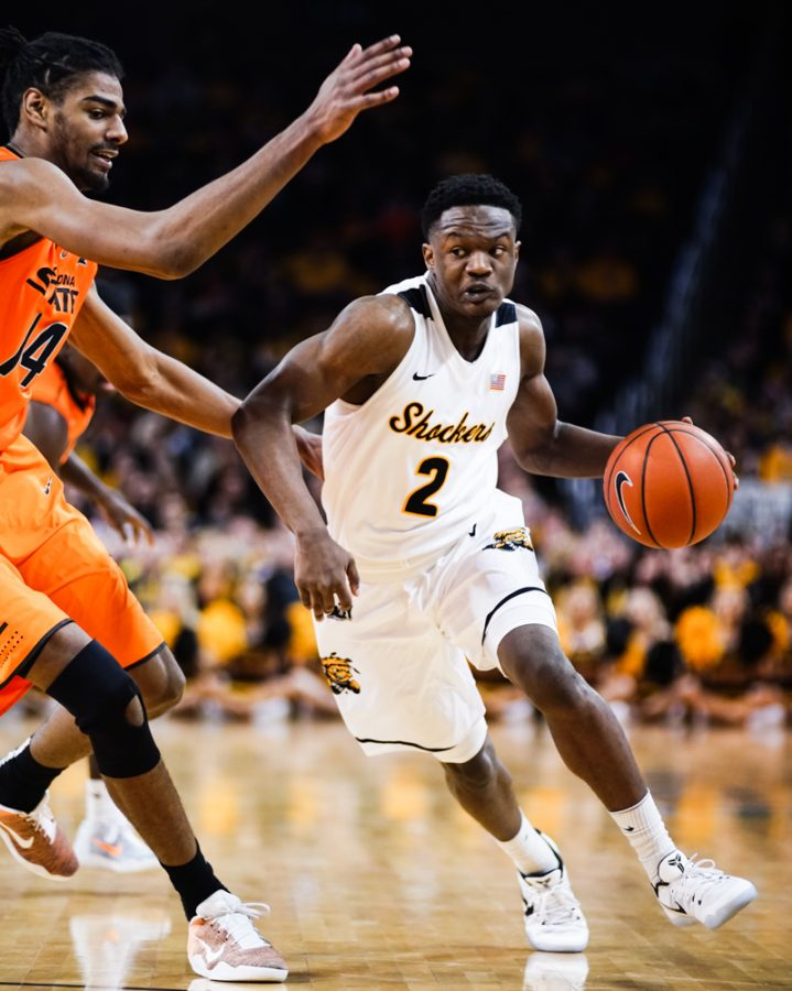 Junior guard Daishon Smith (2) drives to the paint against an OSU defender in the first half during the annual INSTRUST Bank Arena game Saturday evening. The Shockers fell to Oklahoma State by the score of 93-76.