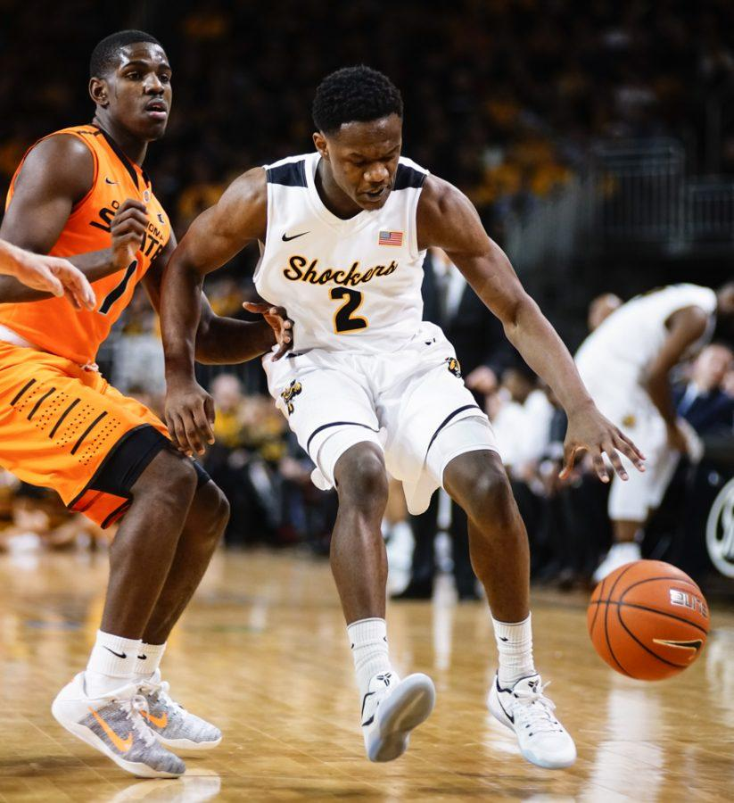 Junior guard Daishon Smith (2) fights for a lose ball against an OSU defender in the first half during the annual INSTRUST Bank Arena game Saturday evening. The Shockers fell to Oklahoma State by the score of 93-76.