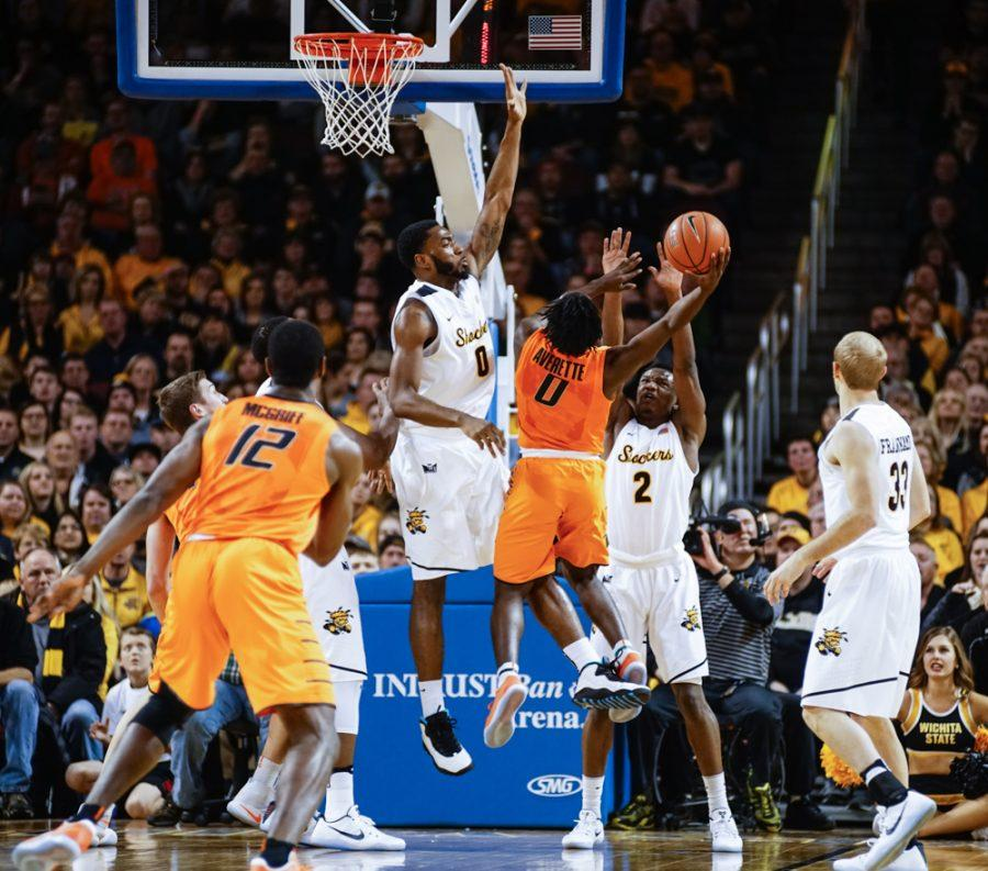 Junior forward Rashard Kelly (0) stretches out for a block against OSU point guard Brandon Averette (0) in the second half during the annual INSTRUST Bank Arena game Saturday evening. The Shockers fell to Oklahoma State by the score of 93-76.