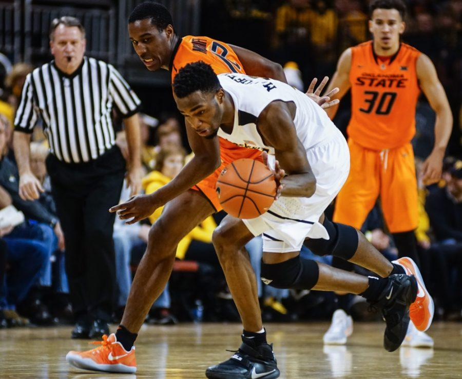 Sophomore forward Markis McDuffie (32) fights for the lose ball against an OSU defender in the second half of the annual INSTRUST Bank Arena game Saturday evening.