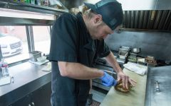 The Flying Stove's chef Rob Schauf cuts the fall chicken sandwich in half, on Nov. 23. The sandwich has roasted chicken, pickled red onions, seared cheese and other tasty ingredients.
