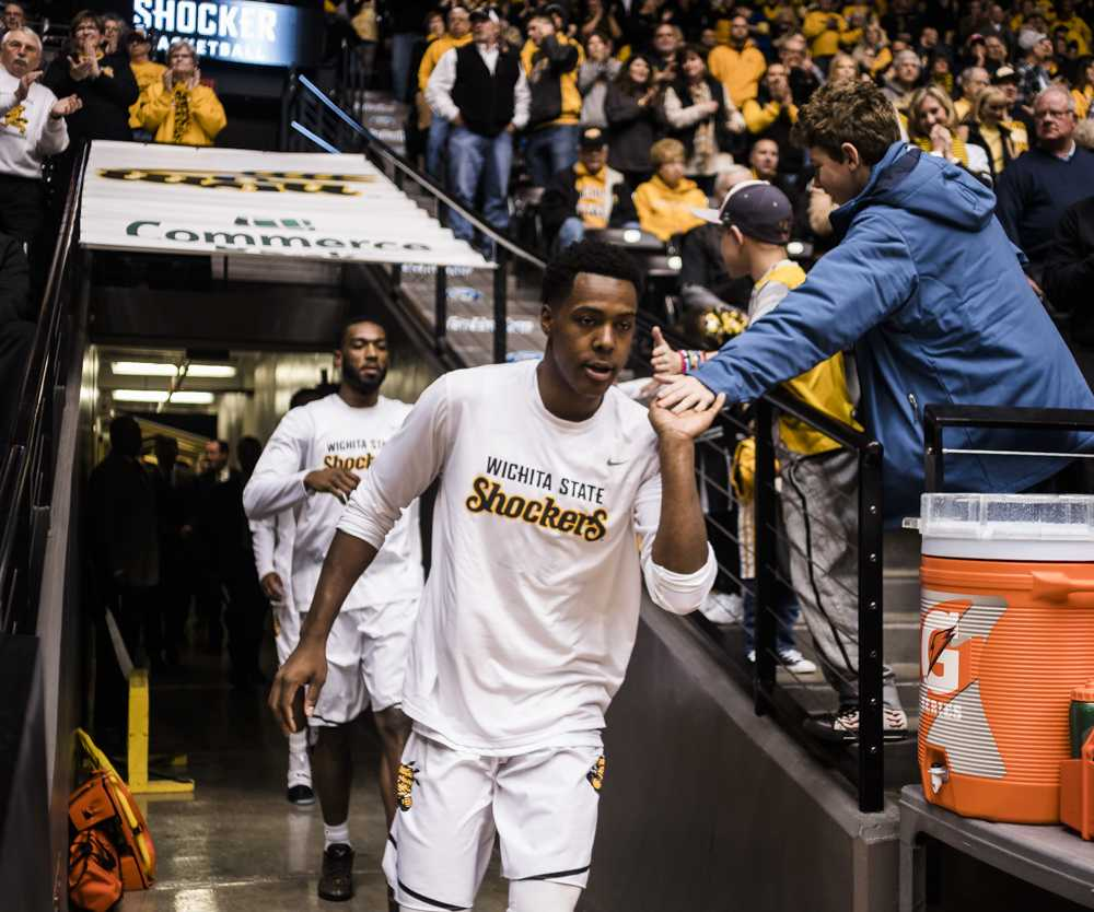 Junior forward Darral Willis, Jr (21) high fives fans prior to the game against Drake Wednesday night at Charles Koch Arena. (Jan. 4, 2017)