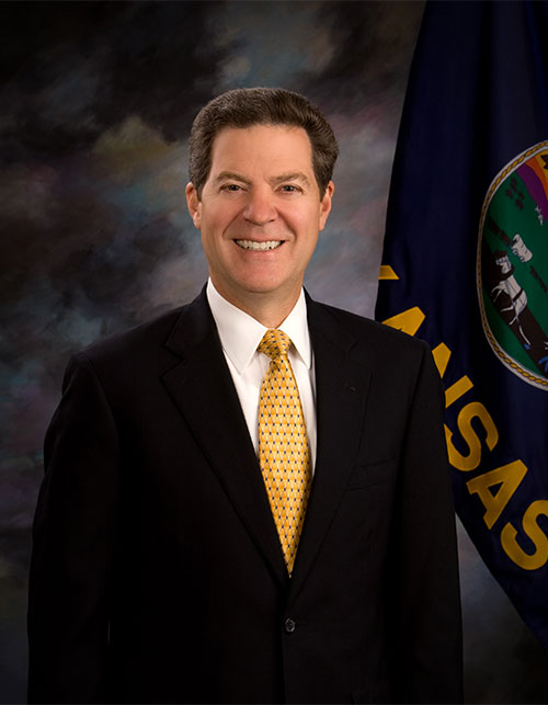 Gov.+Sam+Brownback+poses+for+a+portrait+beside+the+Kansas+flag.