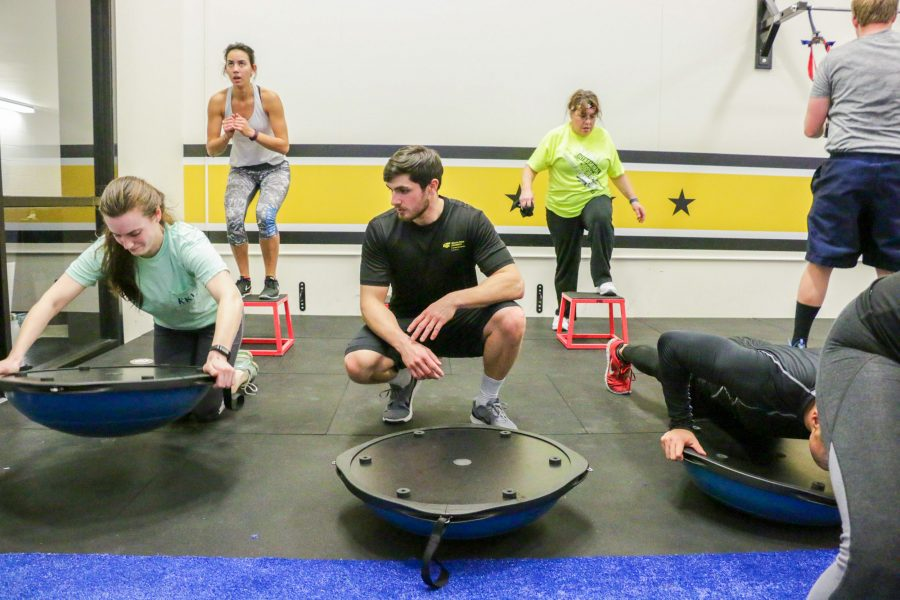 Senior Eddie Pfluger, center, encouraged F45 attendees during Mondays cardio class. Each F45 class has two instructors who help with form, keep people on track and boost encouragement.