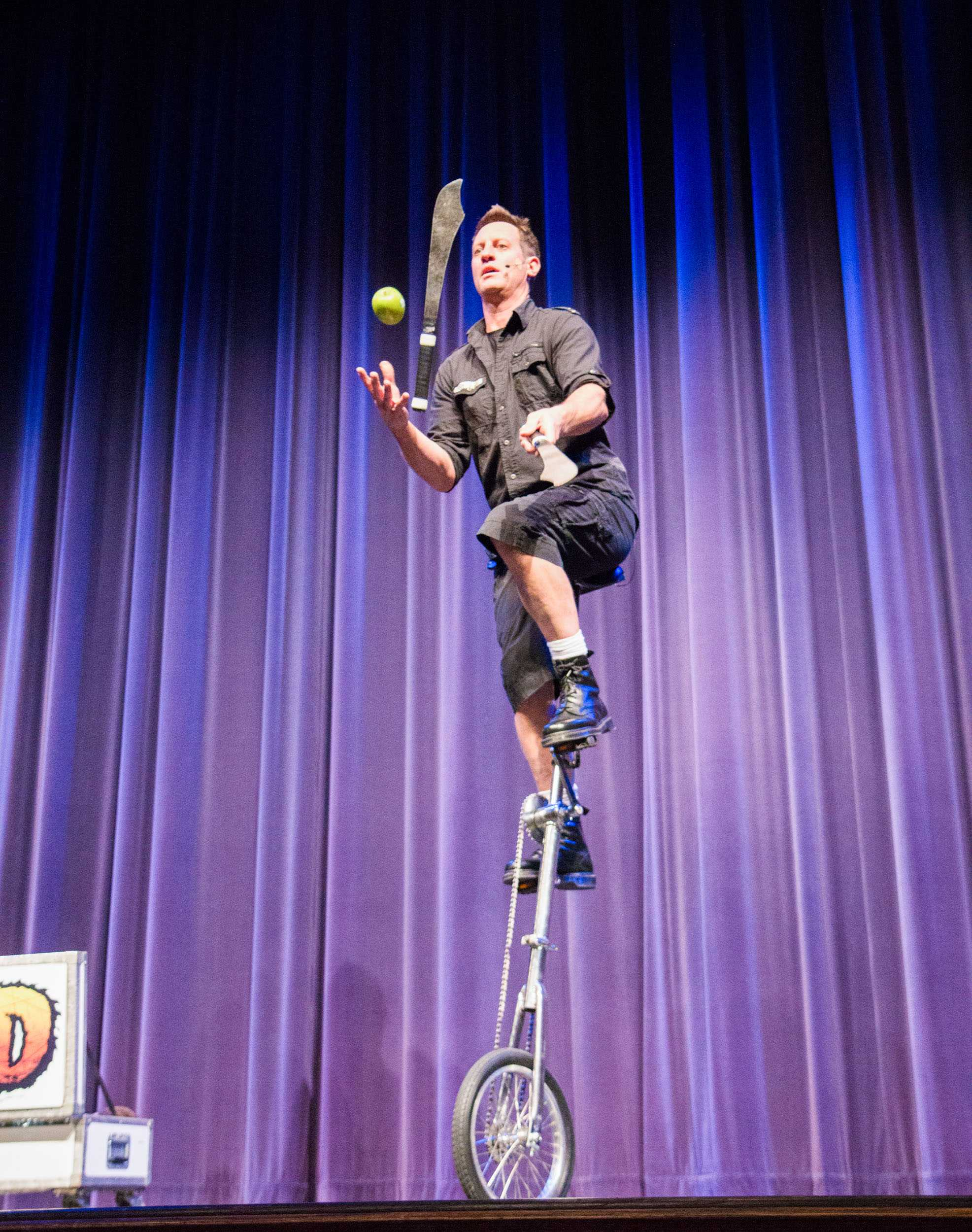Mad Chad juggles two knives and an apple while riding a unicycle during his show at the CAC Theater Saturday night.