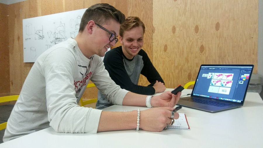 Photo by Sam Belsan Freshmen Spencer Steinert (left) and Jared Goering are working on a new coding device designed for children. Children will build and code the wearable device themsevles.