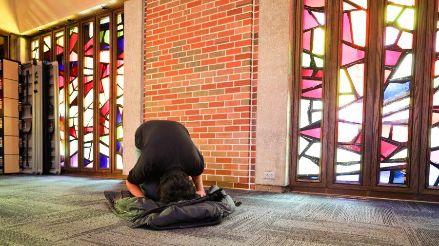 Danial Imran uses his jacket as a prayer mat while doing the Asr prayer in the Interfaith Prayer space on Wednesday. (Feb. 8, 2017)