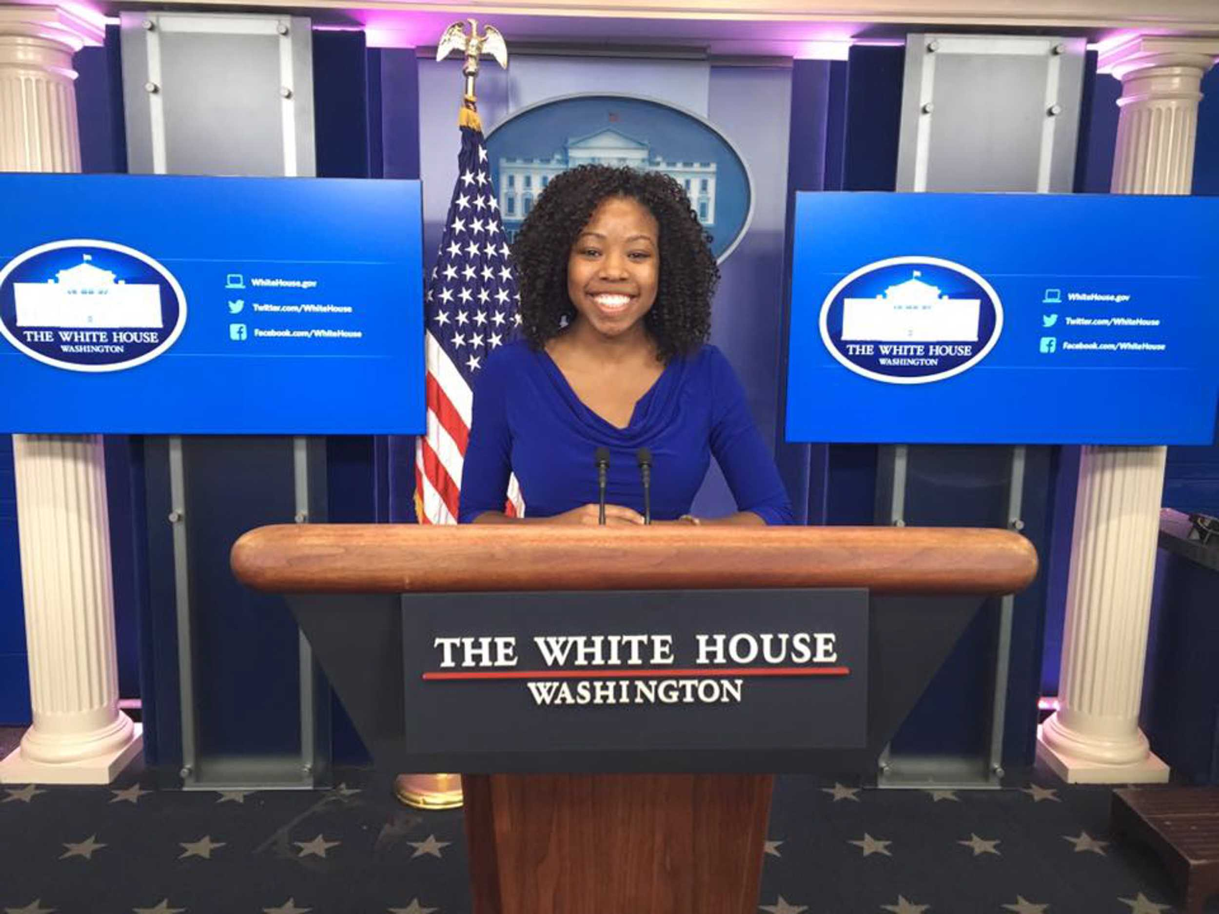 Senior Kiah Duggins poses in the White House briefing room, where then-press secretary Josh Earnest gave the daily press briefings to news media. Duggins served as a policy intern for first lady Michelle Obama's office during the fall semester.