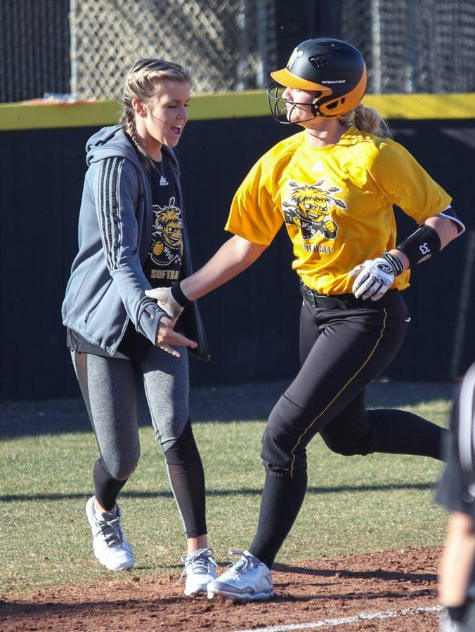 Injured pitcher Jenni Brooks cheers on Ryleigh Buck after she hits a homer in the scrimmage on Feb. 7, 2017. Brooks coached third base during the scrimmage. Brooks has continued to find ways to be involved with the team despite her injury.