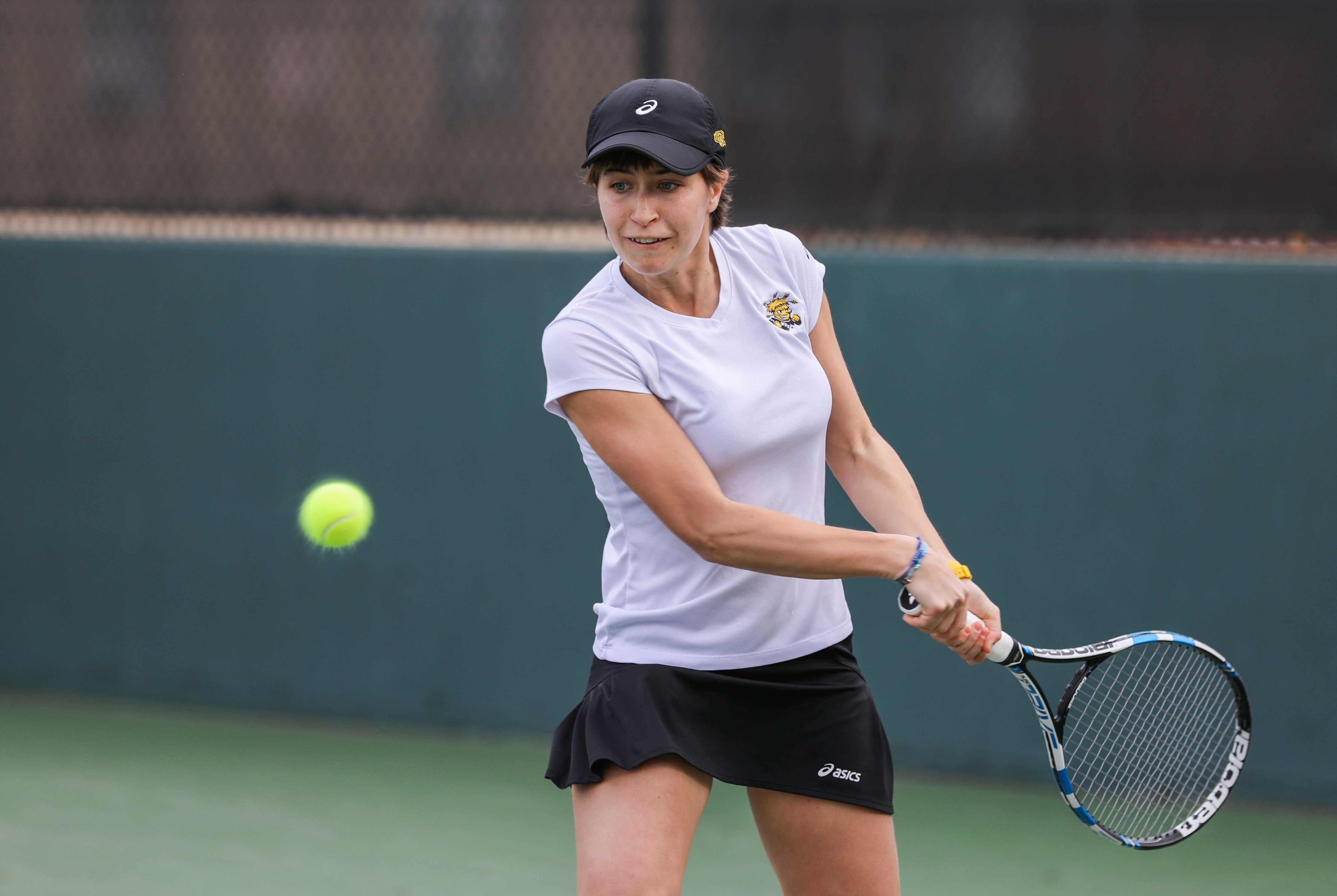 Wichita State Junior Guilia Guidetti takes a backhand swing in a singles match Friday against Kansas. The Shockers lost to the Jayhawks 2-5, ending Wichita State's 34-match home win streak. (Feb. 17, 2017)