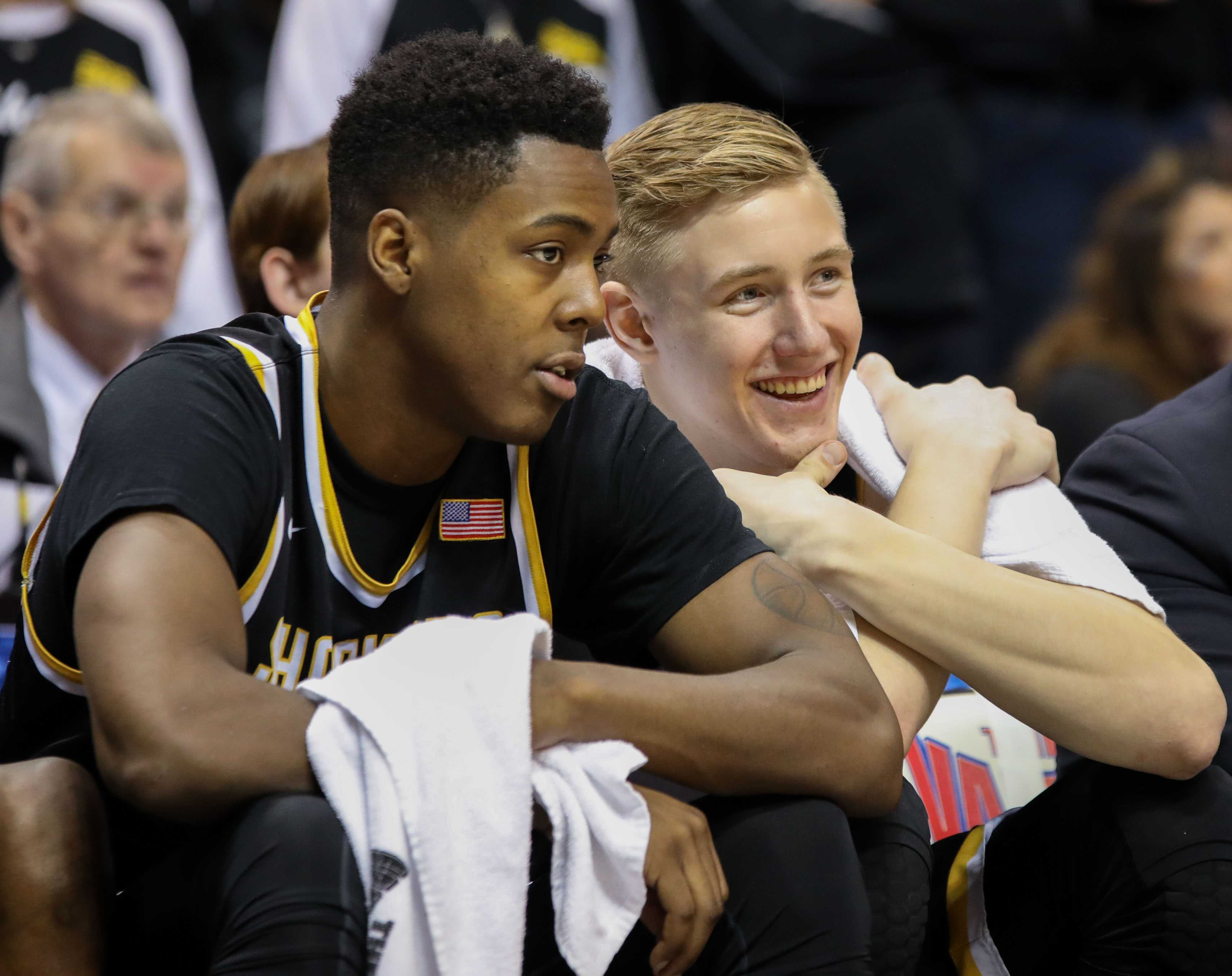 Wichita State's Darral Willis (21) and Rauno Nurger (20) sit on the bench. Nurger grins, realizing Wichita State is going to win.