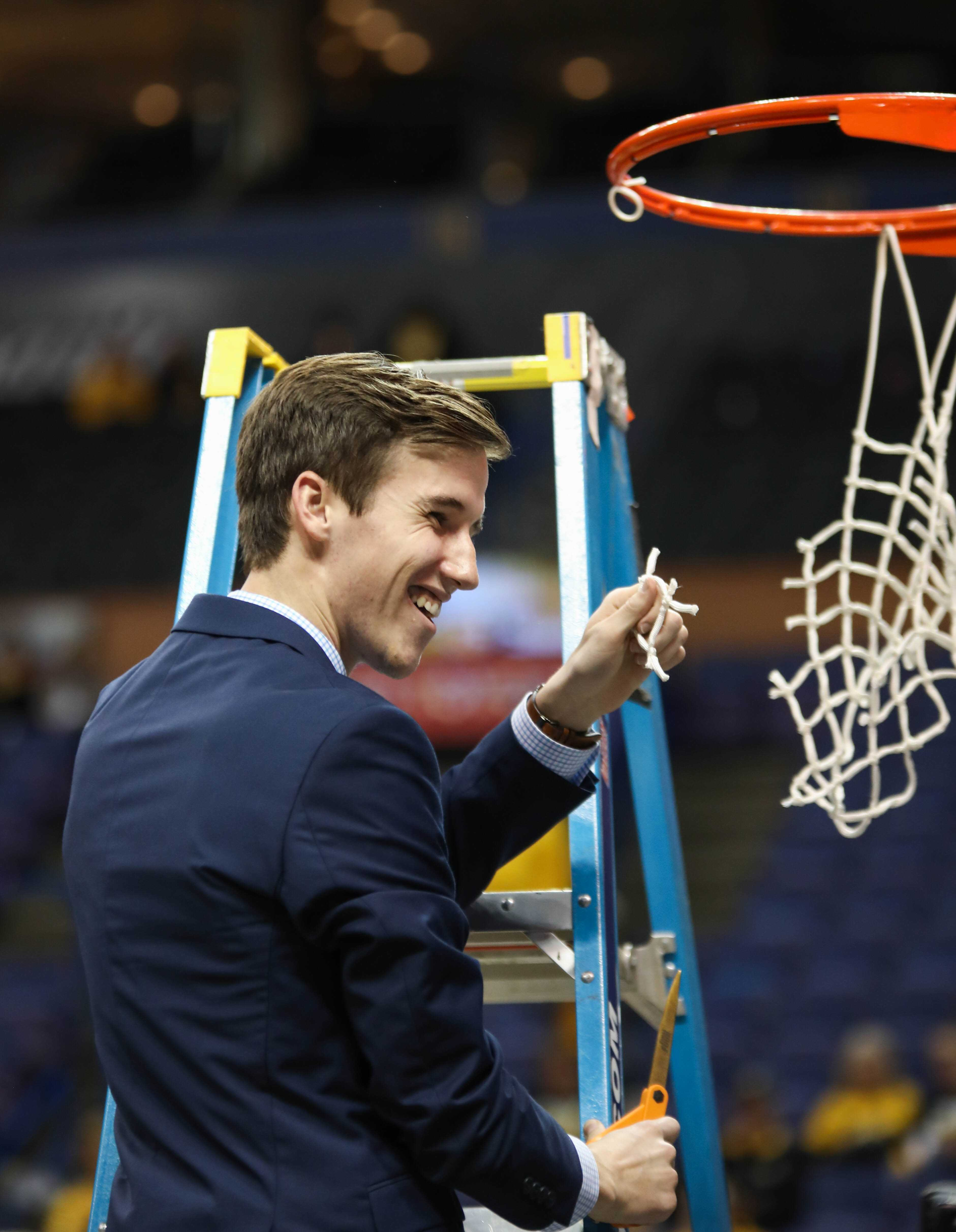 Kellen Marshall holds up his piece of the Missouri Valley Conference Tournament Championship net. Kellen is Gregg Marshall's son, and the head manager for the men's basketball team.