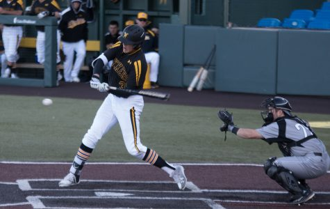 Sophomore Greyson Jenista hits the ball and advances to first base in a game against Omaha.