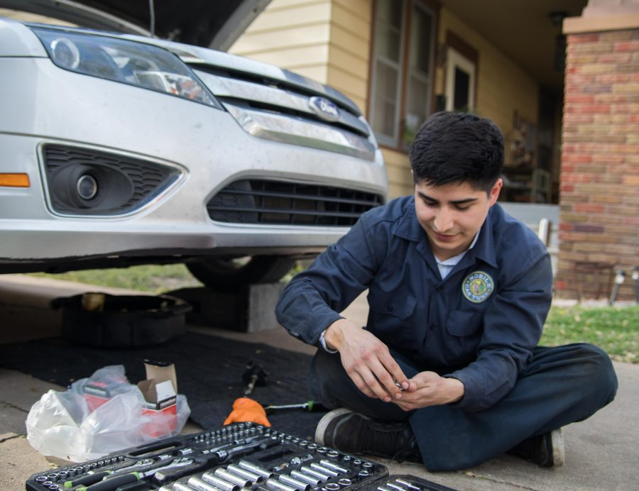 Ernie Cisneros puts his tools back while completing an oil change for his client Dan Edwards on Wednesday evening. Cisneros owes a business called Mobile Car Tune that performs car maintenance services at people's homes.