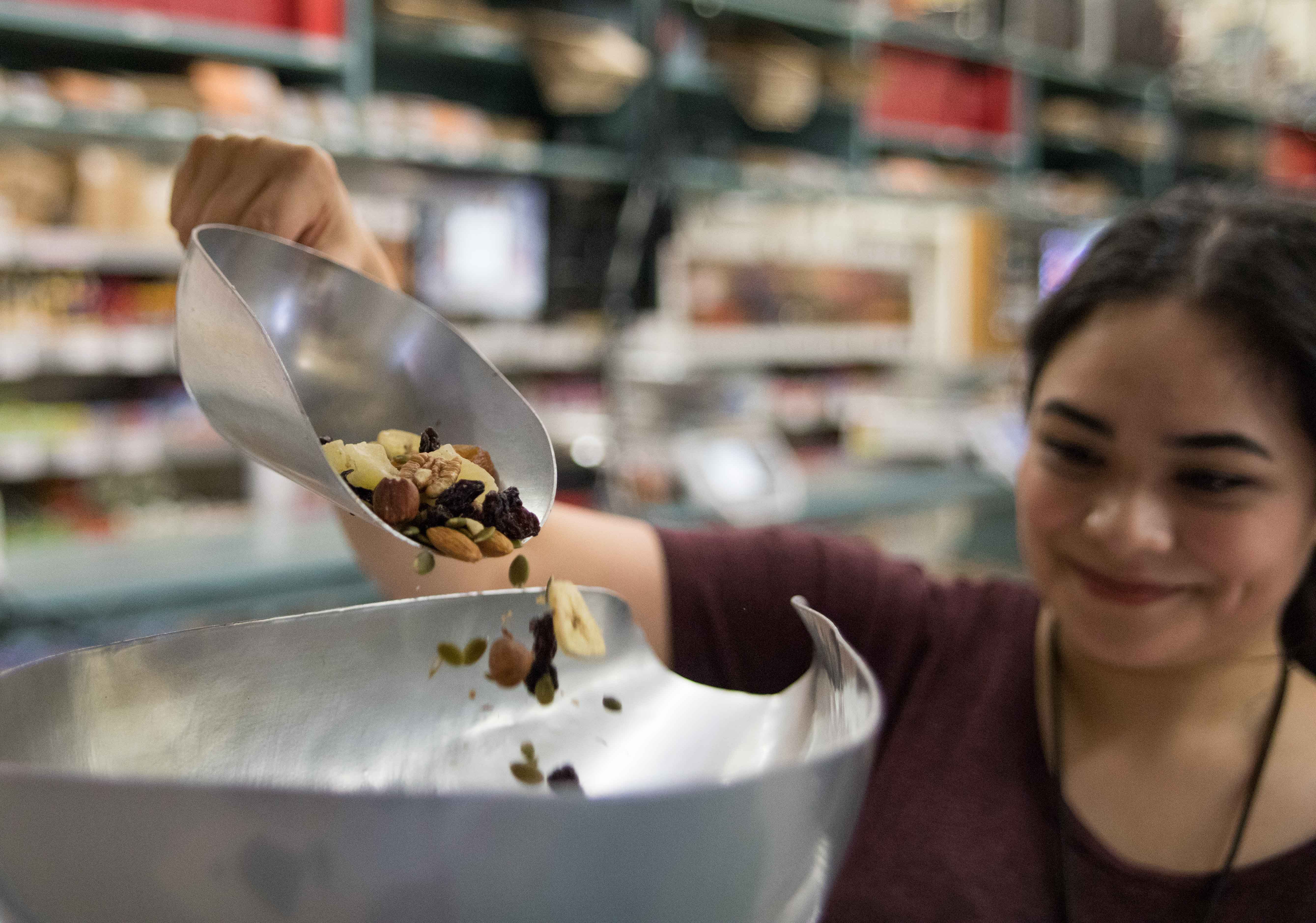 Cashier Vanessa Vazquez weighs out a half pound of the Nifty Nut House's tropical mix for a customer on Tuesday evening. The Nifty Nut House is a third generation family-owned business that was established in 1937.