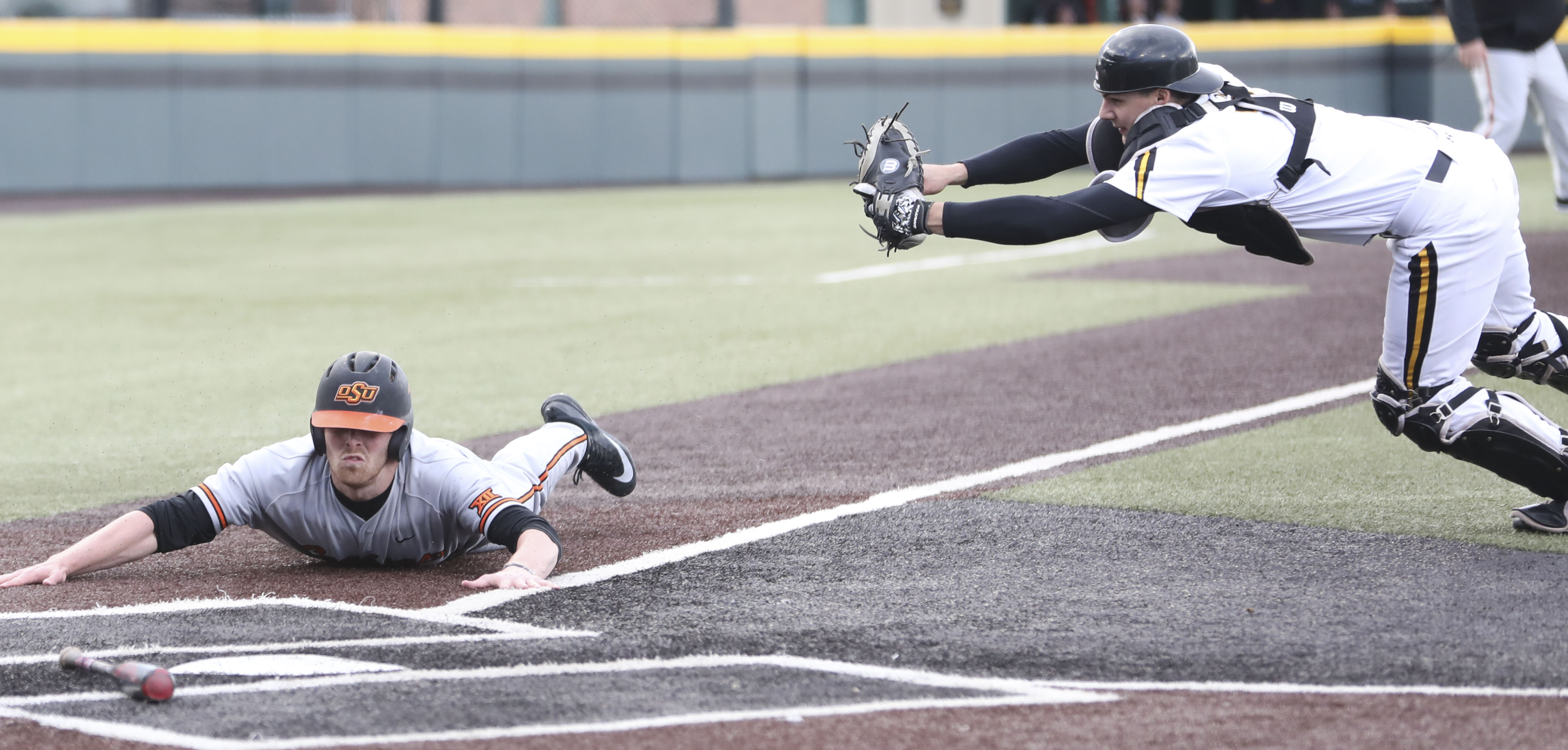Oklahoma State infielder Cameron Dobbs scores against Wichita State catcher Noah Croft in the second inning during Wednesday's game in Eck Stadium. (April 5, 2017)
