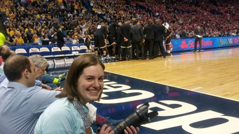 Hannah Roberts sits courtside as she photographs Wichita State in the Missouri Valley Conference Tournament Championship game in St. Louis. (March 5, 2017)