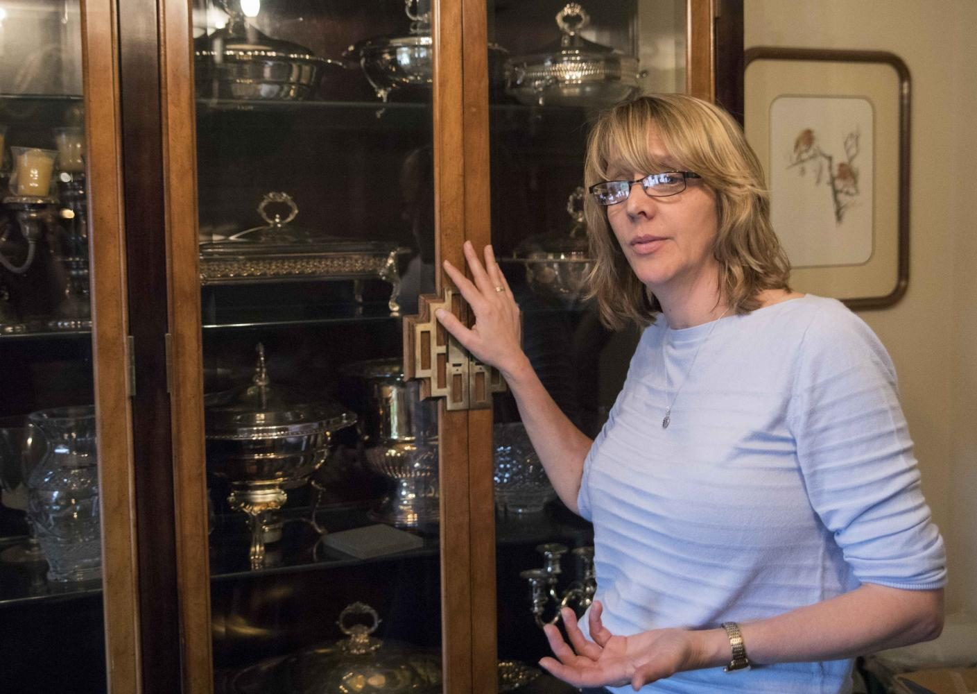 Elizabeth Beugelsdyk closes a cupboard after looking at the silver in an estate sale she is running for the business she owns with her cousin called L&L Family Estate Sales.