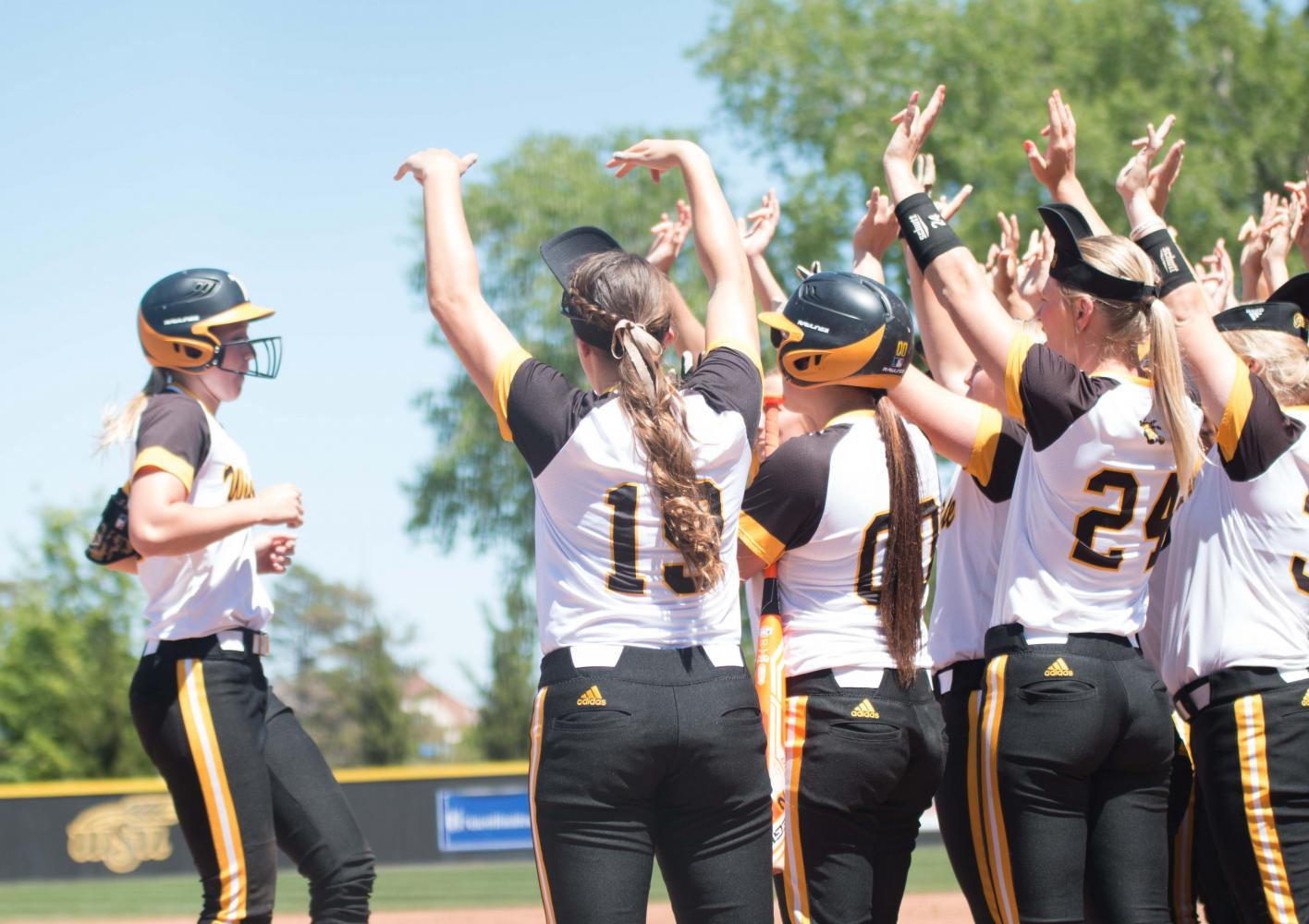 Members of the Shocker softball team greet sophomore Laurie Derrico after a home run against Evansville.