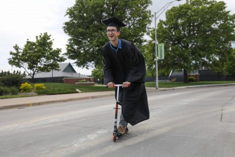FILE PHOTO: Wichita State student Evan Pflugradt blissfully scoots his way into graduation.