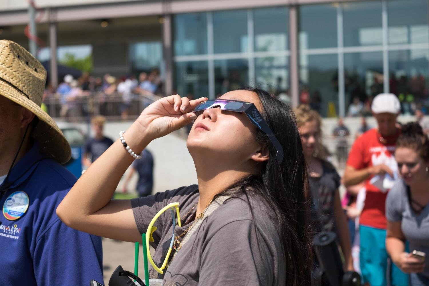 Tana+Thongsing%2C+a+senior+student+at+Wichita+State%2C+is+using+eclipse+glasses+to+look+at+the+solar+eclipse.