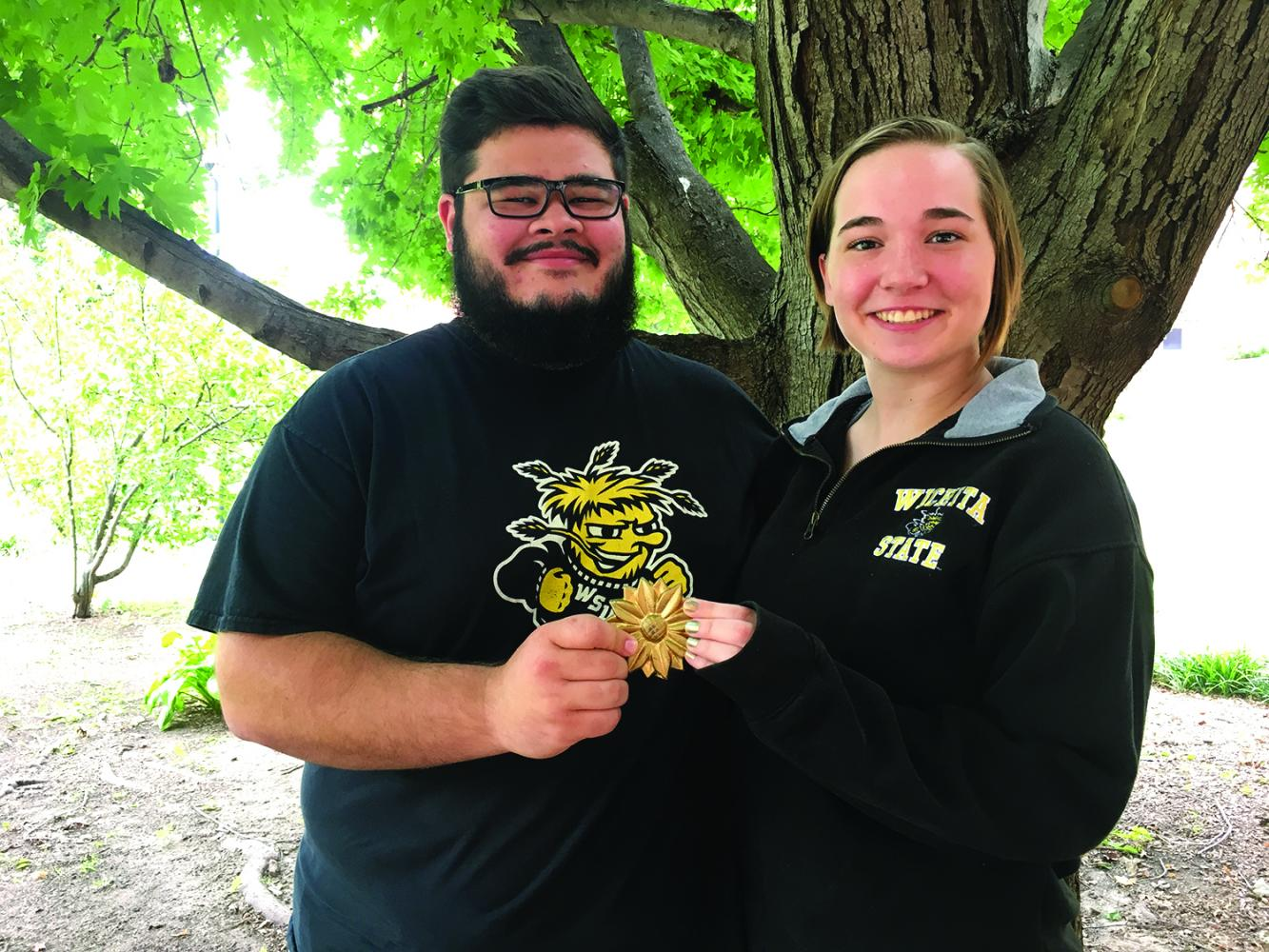 The Sunflower Medallion Hunt winners hold their coveted quarry. Connor Burden, left, and Megan Singleton, right, found the medallion Saturday evening, after six clues.