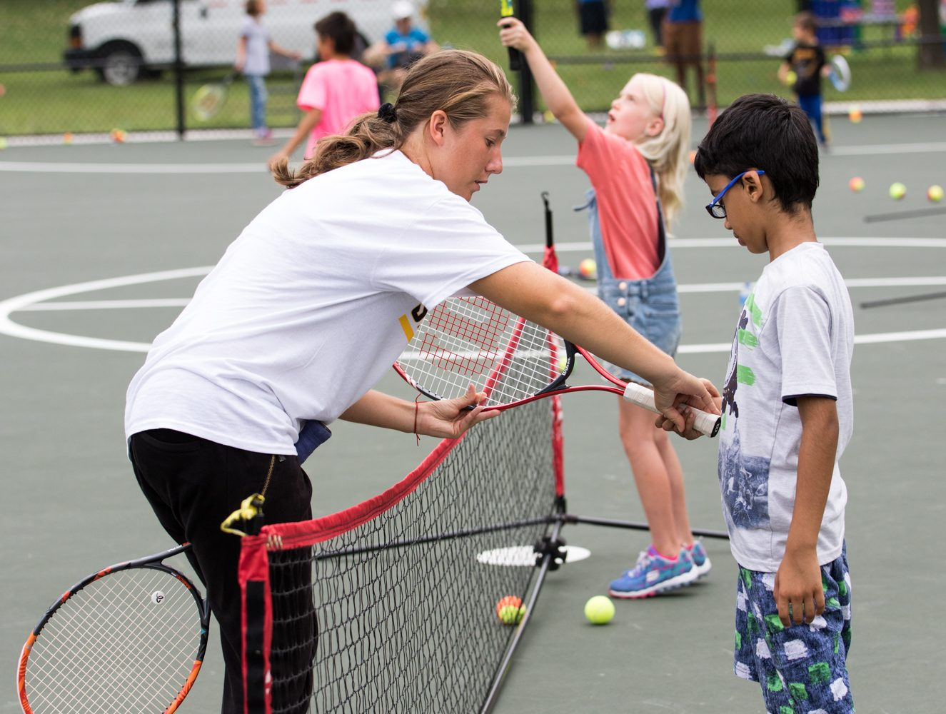 Alexandra Lazarova shows a youth at the clinic how to hold the tennis racket.