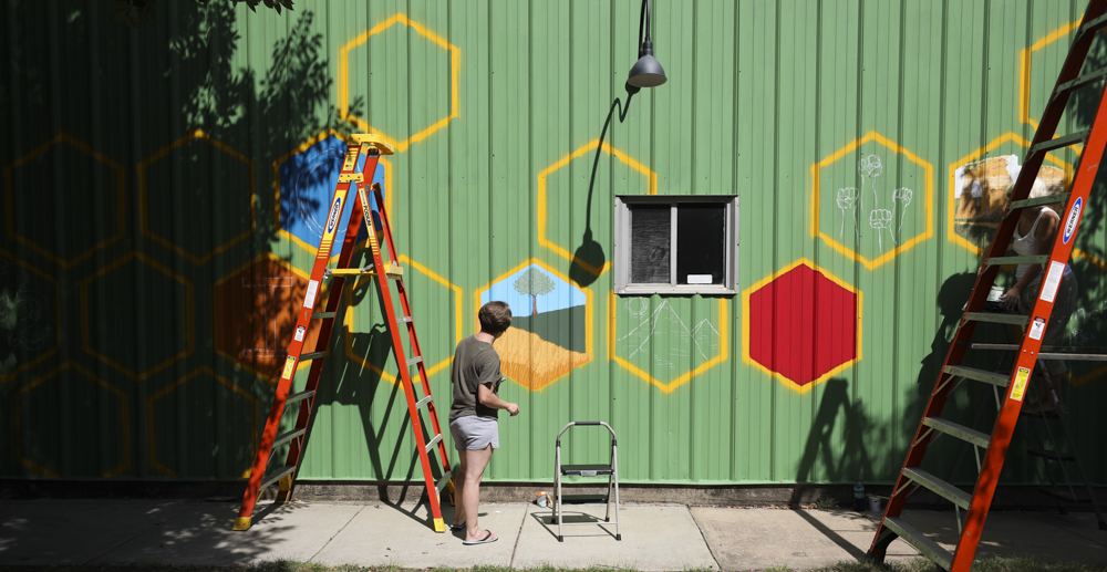 DeMay Grunden works on the mural on the side of Central Standard Brewing. Abram Howell and Margi Ault-Duell and Hugo Pérez Trejo designed the modular, honeycomb-esque piece for Avenue Art Days. Each hexagon will contain a unique representation of Wichita Iconography.