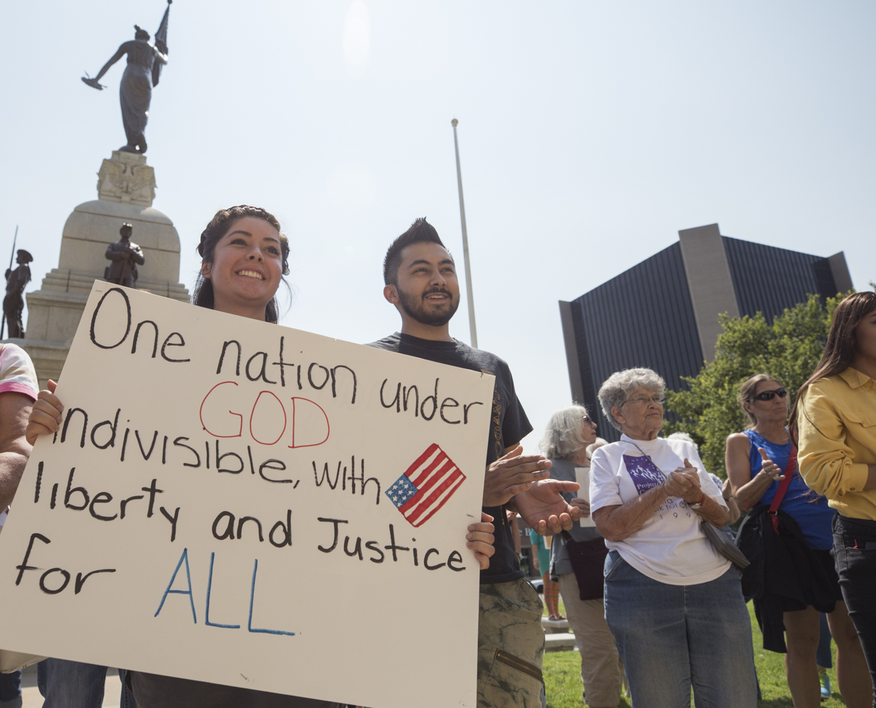 Wichita State Students Karen Segura and Jaime Segura hold up a sign and applaud during the #HereToStay support event held at the Historical County Courthouse on Tuesday afternoon. (Sept. 5, 2017)