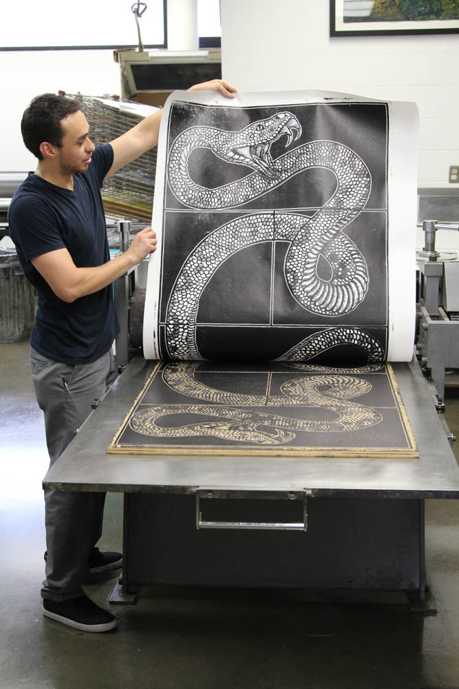 Marco Hernandez, teacher of print making, takes first look at a print finished Sept. 27. He checked his print a second time after rolling it.
